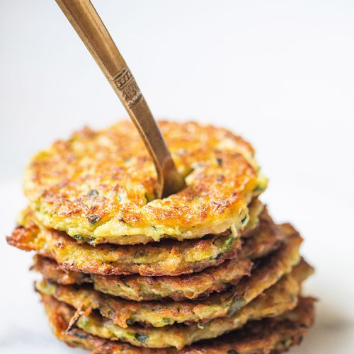 zucchini fritters stacked on top of each other with a brass fork inside them placed on a white marble board