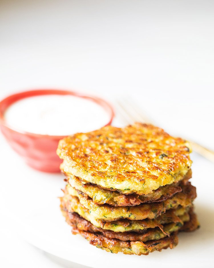 zucchin fritters stacked and kept on white marble board with sour cream in a red bowl kept in the background