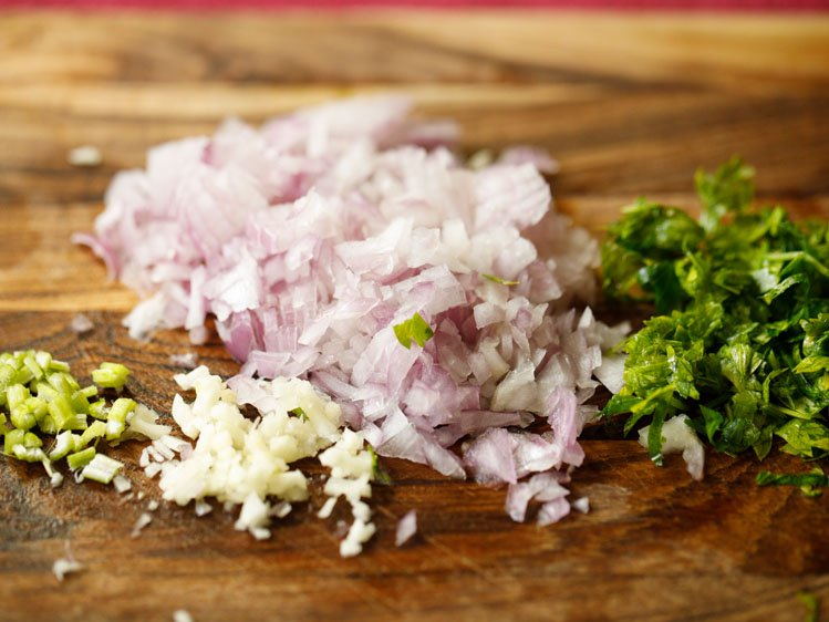 finely chopped onions, garlic, parsley and celery on a chopping board