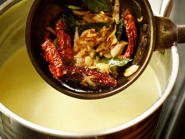 pan with tempered spices and chilies above moru curry or pulissery