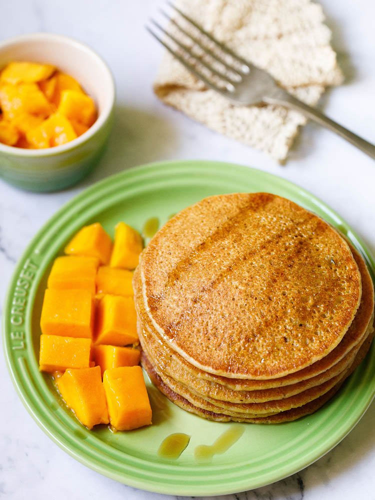 pumpkin pancakes stacked on green plate drizzled with maple syrup with a side of cubed mangoes and a small bowl of cubes mangoes on the top
