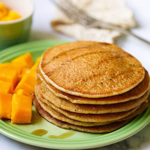 pumpkin pancakes stacked on green plate drizzled with maple syrup with a side of cubed mangoes