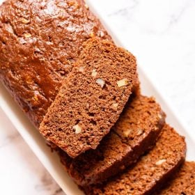 chocolate zucchini bread partly sliced with one slice kept on top of the loaf on a white rectangular tray on a white marble background