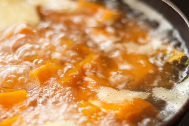 simmering pot of water and pumpkin cubes