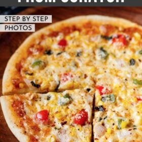 """a triangular slice of veg pizza with the remaining pizza on a wooden pizza plate with a bold text of """"Veg Pizza from Scratch"""" listed on top of image"""