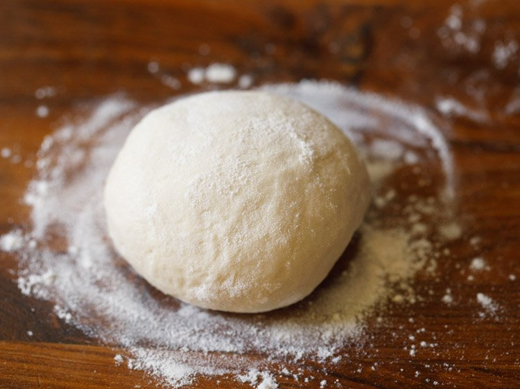 a dough ball dusted with flour on a wooden board