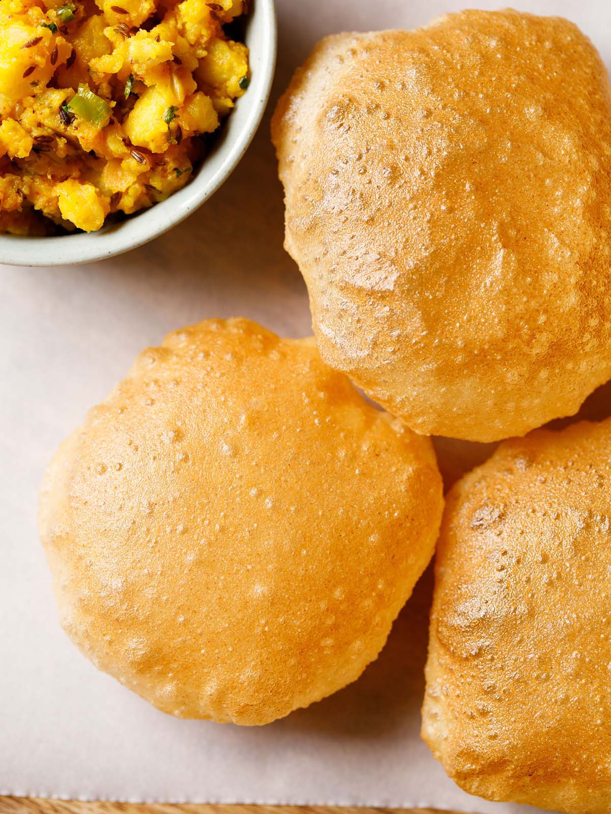 homemade puri placed on parchment paper with a side bowl of spiced sautéed Indian potato dish