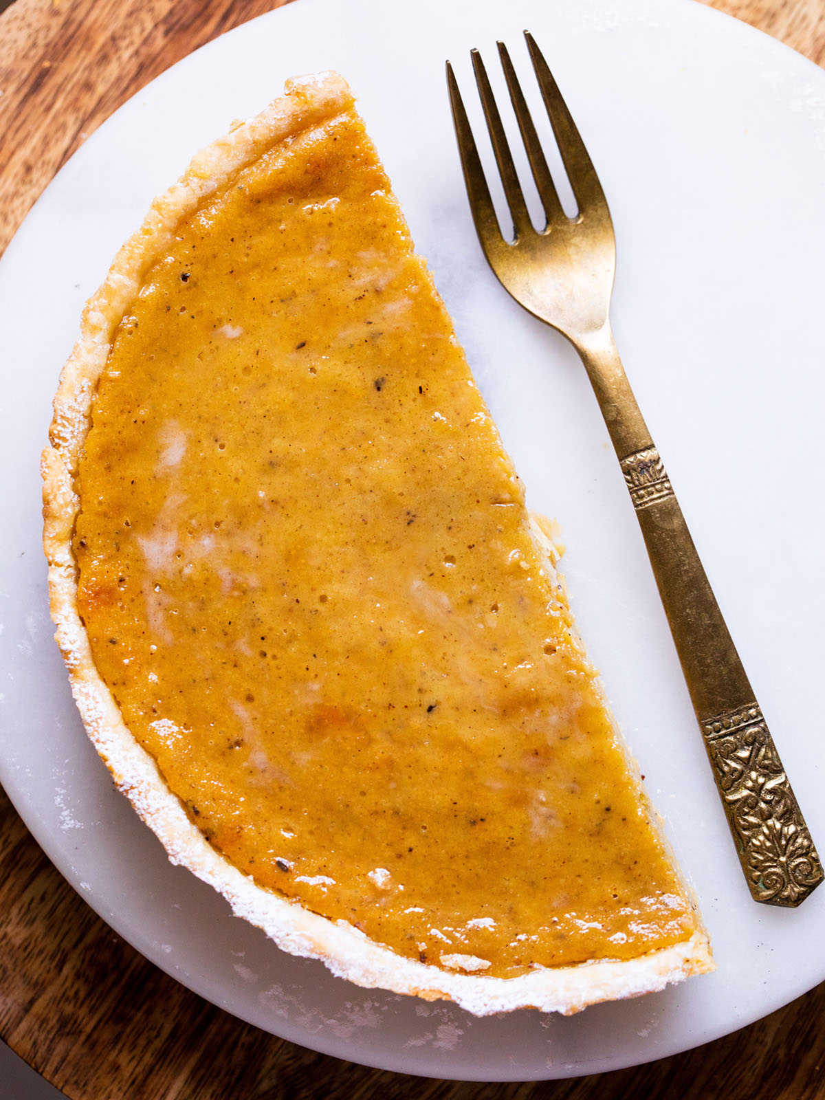half of an eggless pumpkin pie in an all butter homemade pie crust on a white serving platter with a brass fork