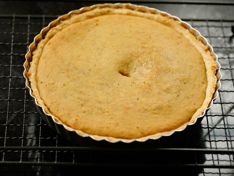 baked eggless pumpkin pie in a silver pie tin on a cooling rack