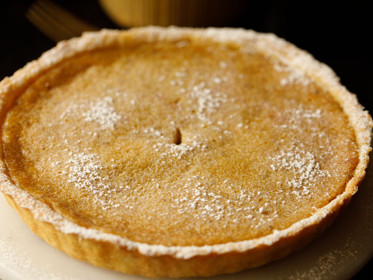 baked eggless pumpkin pie on a white serving platter dusted with confectioner's sugar