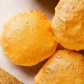 perfect golden puri placed on white parchment paper