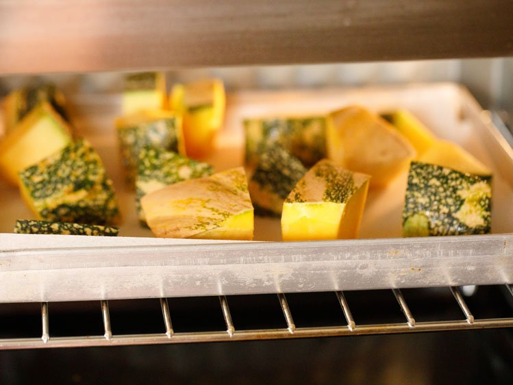 cubed kabocha squash on a parchment lined baking sheet in the oven