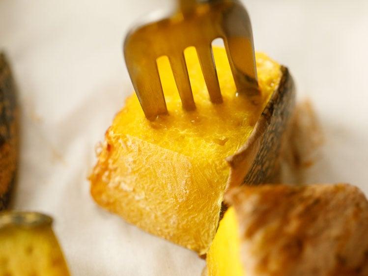 silver fork piercing a cube of roasted kabocha pumpkin
