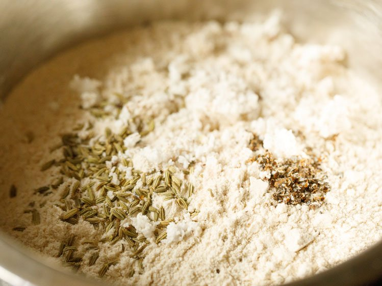 whole wheat flour, salt, fennel, dessicated coconut and cardamom in a mixing bowl