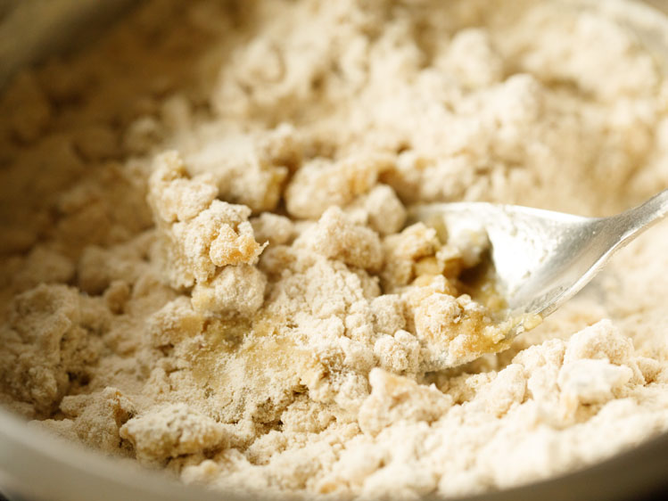 dry flour mixture after mixing with ghee in a silver mixing bowl with a silver spoon