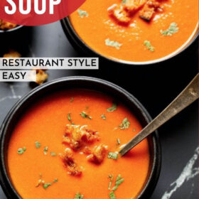 """homemade rustic tomato soup from scratch in a black wooden bowl with a silver spoon topped with croutons and parsley with a bold font of """"Tomato Soup"""" listed on photo"""