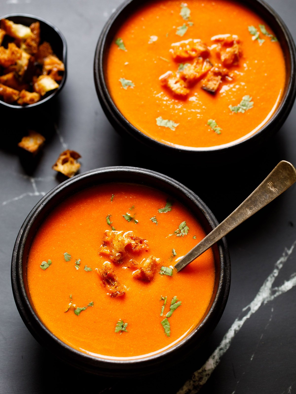 tomato soup in a black wooden bowl with a silver spoon topped with croutons and parsley