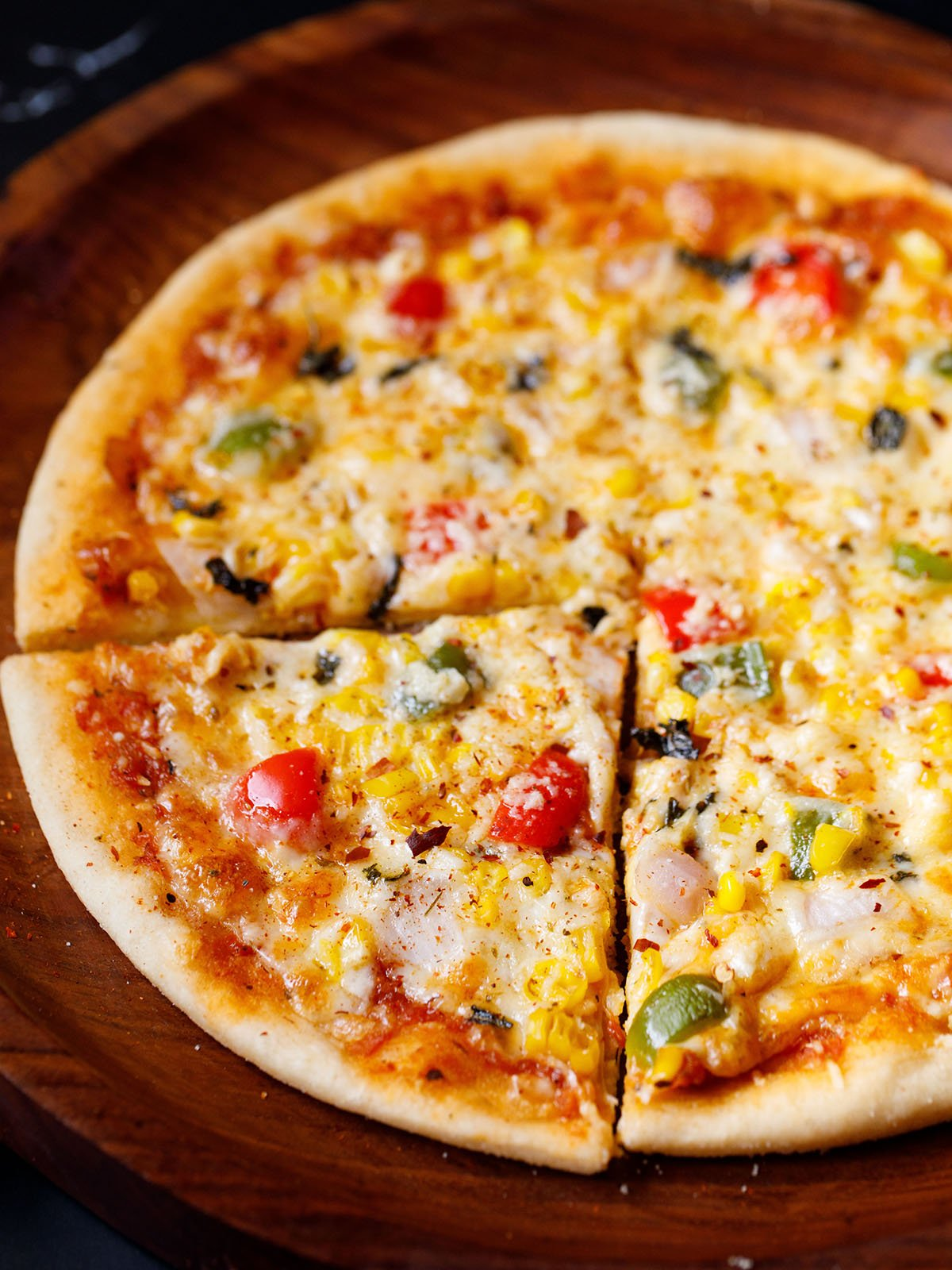 a triangular slice of veg pizza with the remaining pizza on a wooden pizza plate sprinkled with some dried herbs and red chilli flakes