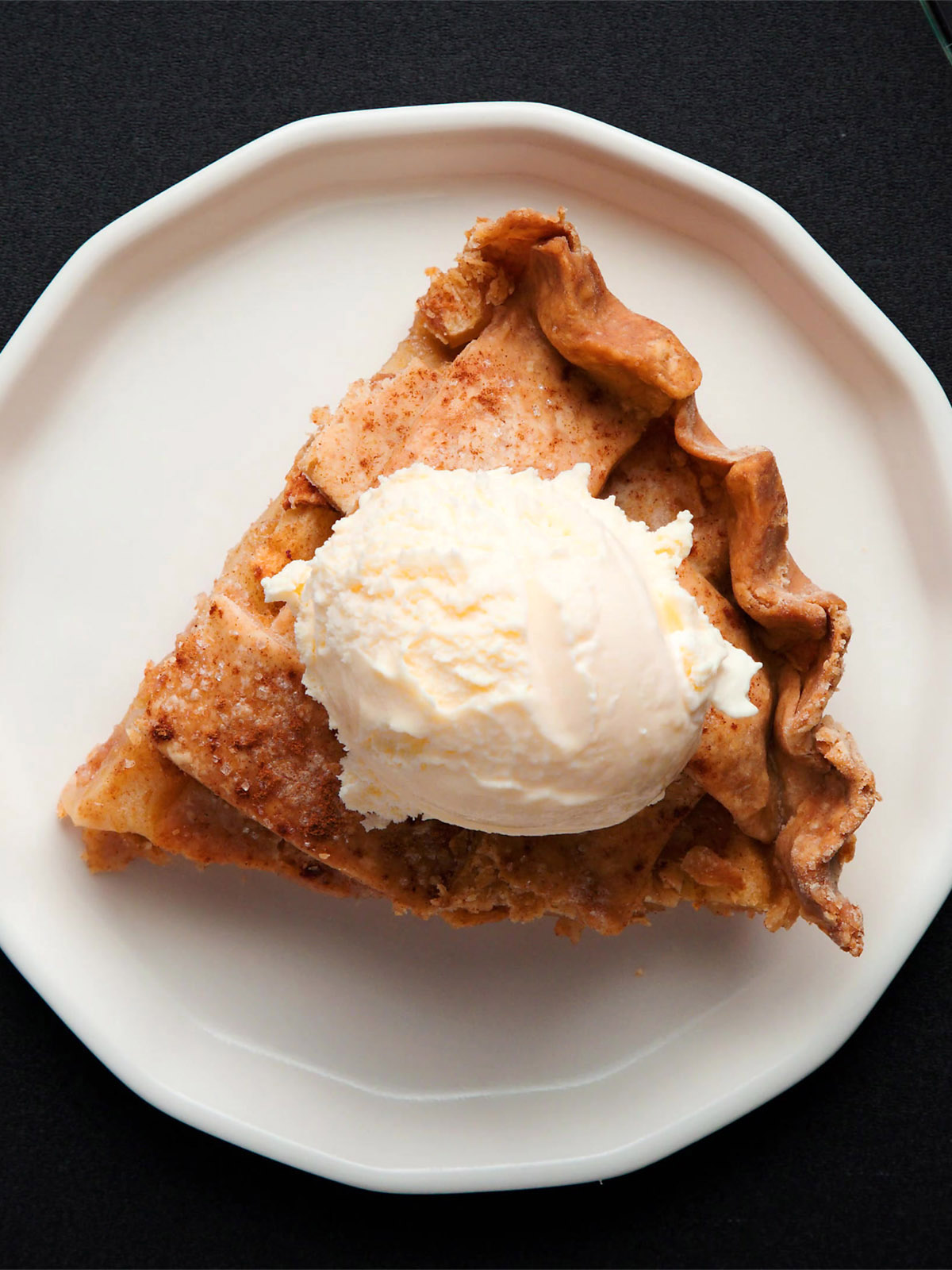 an apple pie wedge slice topped with vanilla ice cream on an off-white plate