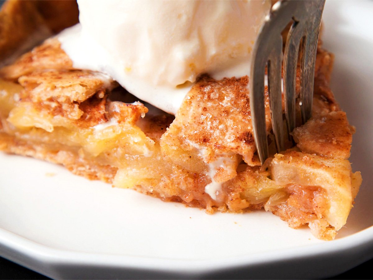 apple pie wedge being cut with a fork