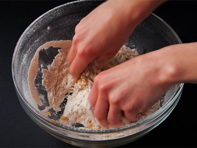 oil being mixed in flour with fingertips