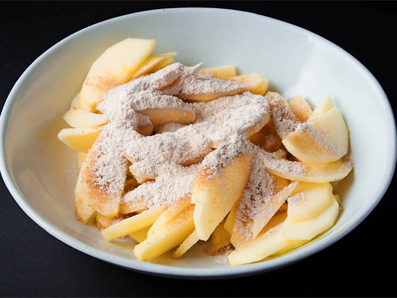 brown sugar and wheat flour added on sliced apples in a white bowl