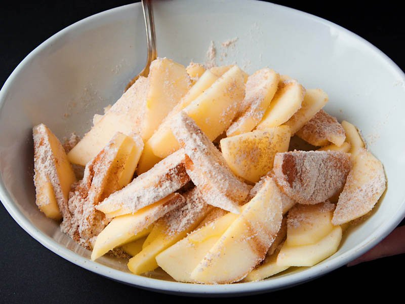 flour and sugar being mixed with apples with a spoon