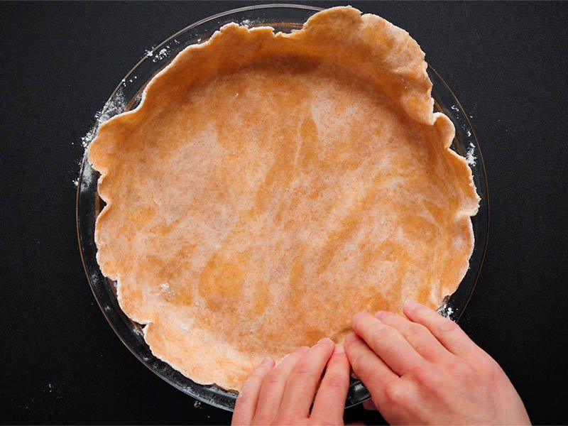 rolled pie dough placed in a glass pie pan and edges being pushed into the pan