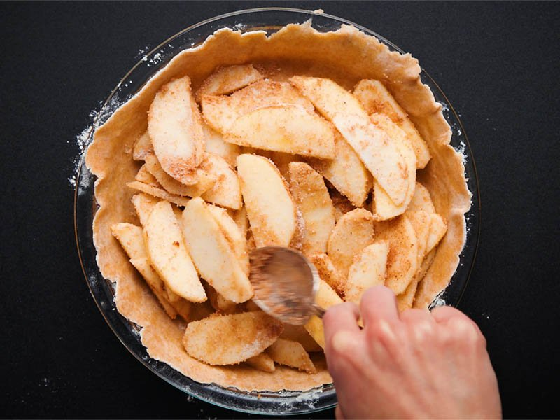 pie crust being topped with apple pie filling