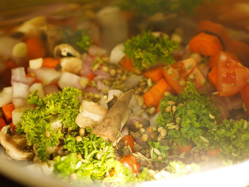 veggies, herbs and spices in the steel insert of the instant pot