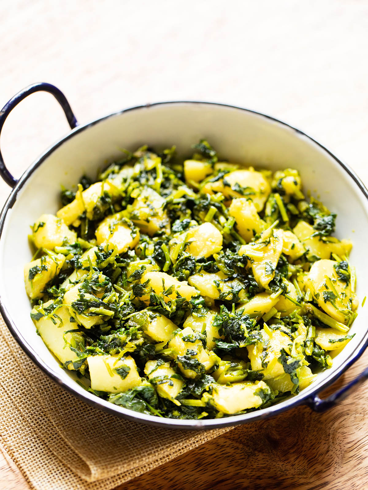 aloo methi in a enameled black rimmed small white wok on a brown jute napkin