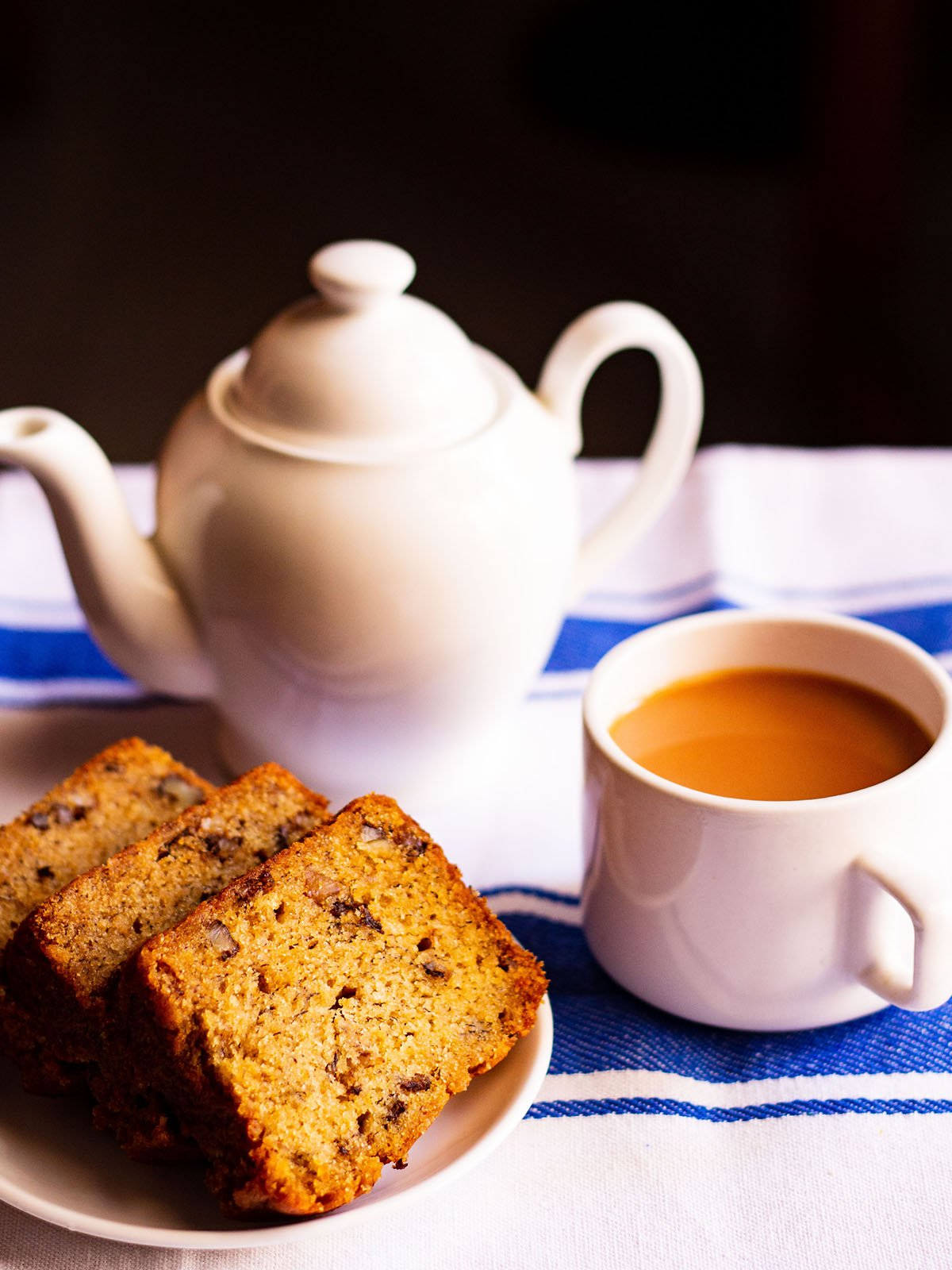 sliced eggless banana cake slices on a white plate with a white cup of tea and white tea pot