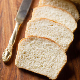 bread slices placed on top of each other with an antique butter knife on a brown wooden board
