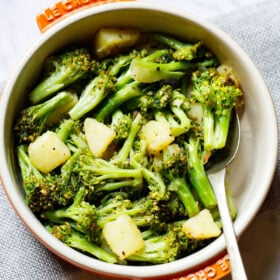 sauteed broccoli in a le creuset cream ceramic pan with orange handles with a spoon inside placed on a folded light gray jute fabric