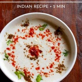 cucumber raita sprinkled with red chilli powder, roasted cumin powder and cilantro in a white bowl on a dark brown wooden board
