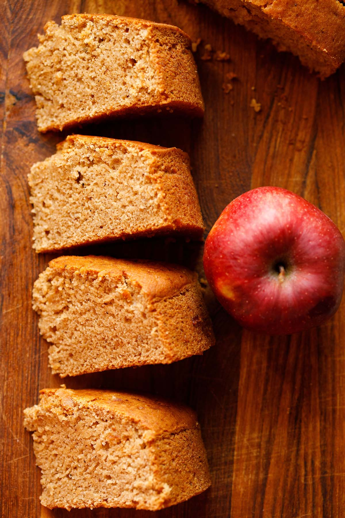 three slices of eggless apple cake on wooden table next to red apple