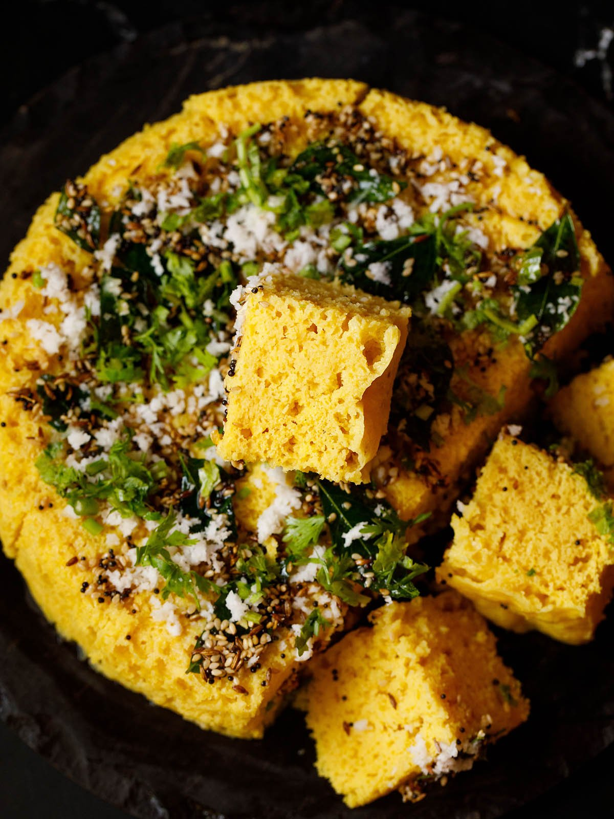 a tender soft block of khaman kept on top the round steamed cake with some khaman cubes at the side on a black granite tray