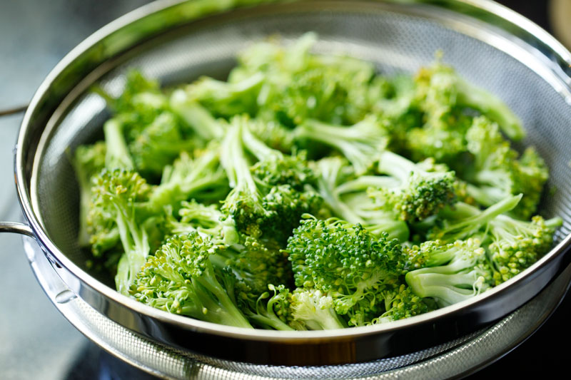 broccoli florets being drained in a steel colander
