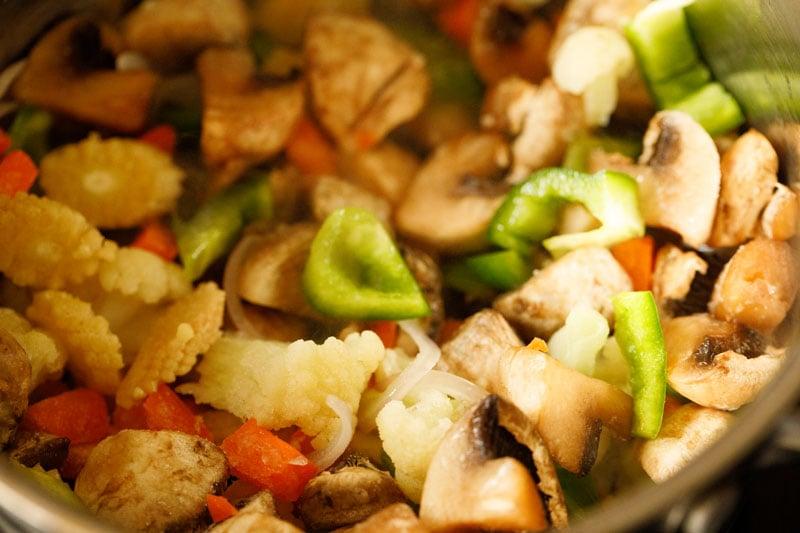 melange of vegetables added to skillet with sautéed mushrooms