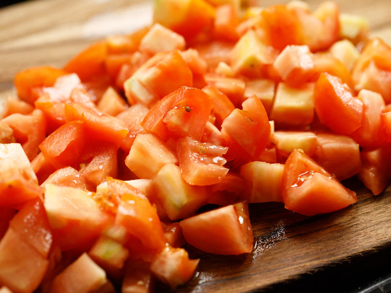 fresh tomatoes that have been cubed on a wooden cutting board