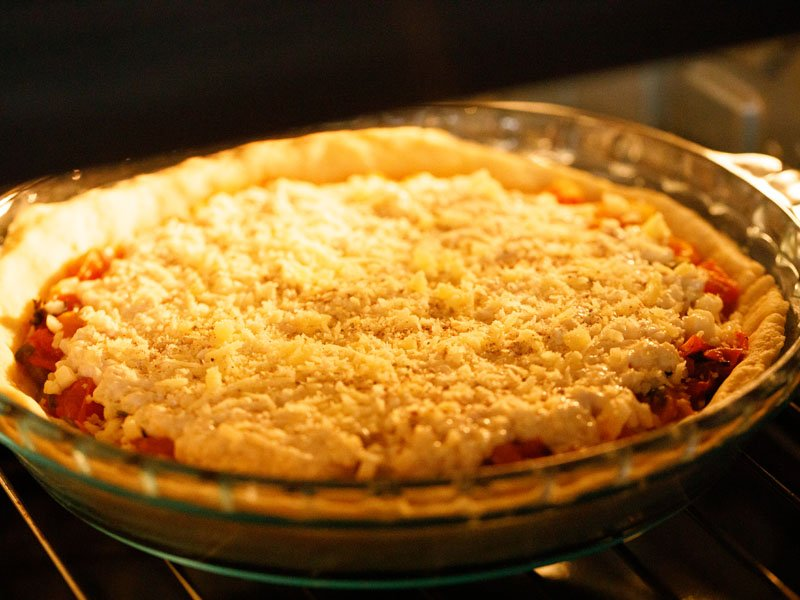 assembled southern tomato pie in a clear glass pie dish in the oven before baking
