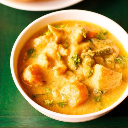 veg kurma or korma in a white bowl on a dark green wooden tray