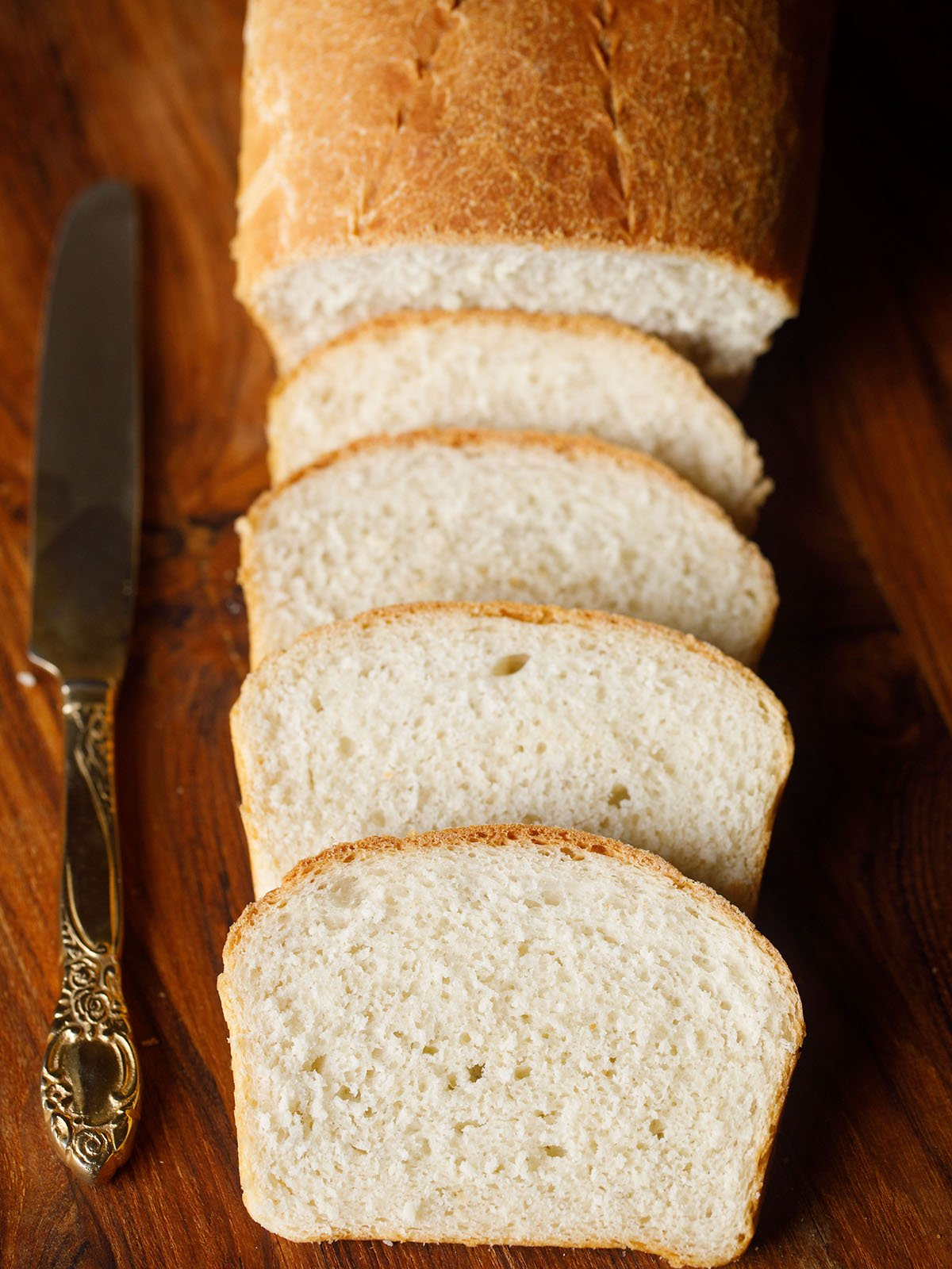 overheat shot of four slices of white bread with a partial view of the loaf with an brass butter knife on a brown wooden chopping board