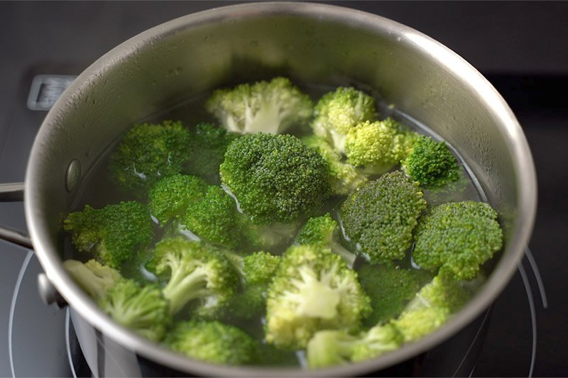 top shot of broccoli in water in pot on stovetop