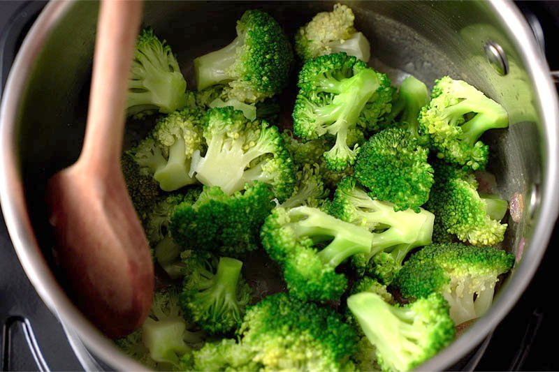 Top shot of wooden spoon stirring broccoli florets in pot