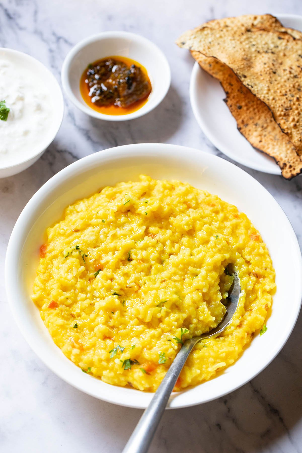 top shot of moong dal khichdi in a bowl with a spoon inside with sides of curd, mango pickle in white bowls and roasted papad served in a white plate