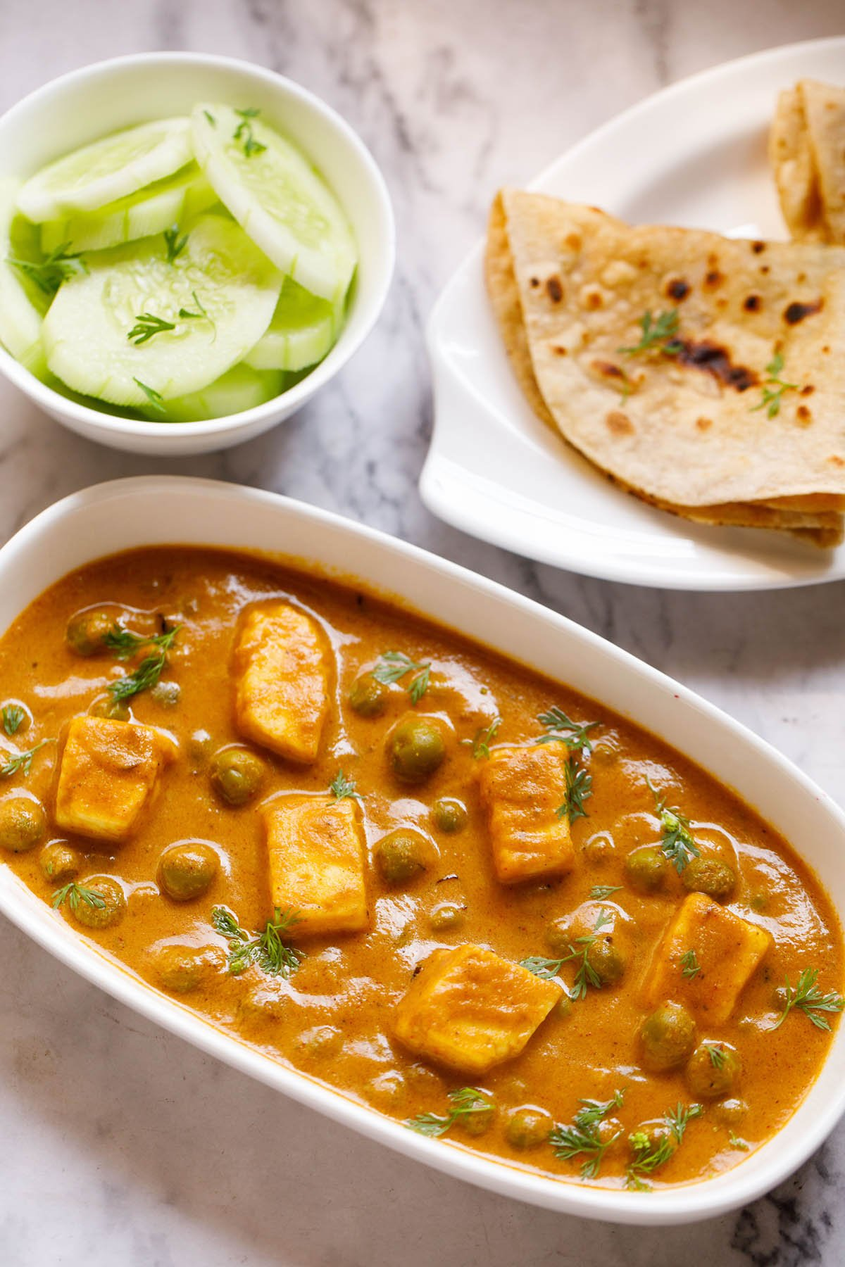 Top shot of matar paneer on white rectangle plate next to sliced cucumber in a white bowl and folded two roti in a white plate sitting on white marble table