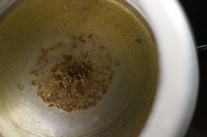 Top shot of cumin seeds sautéing in pressure cooker