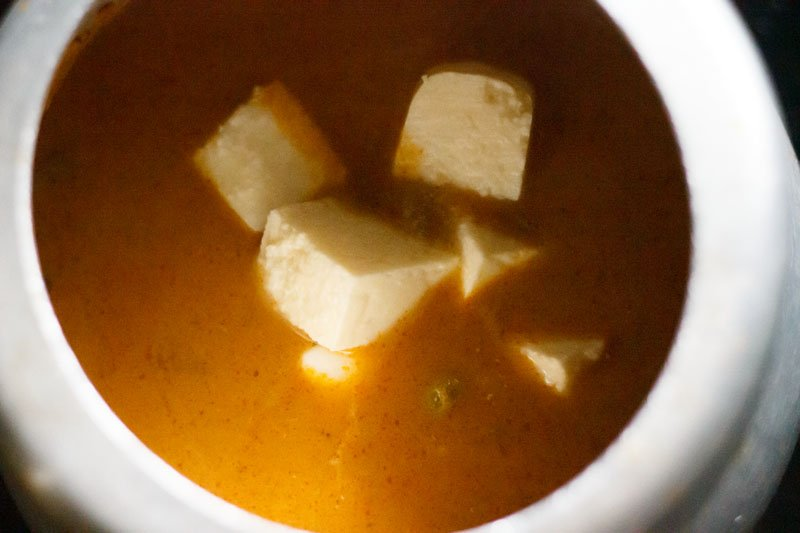 Top shots of paneer cubes in liquid masala and pea mixture, sitting in pressure cooker