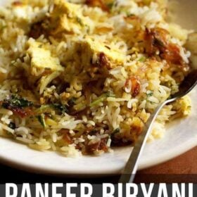 paneer biryani served in a cream shallow plate with a steel spoon by the side